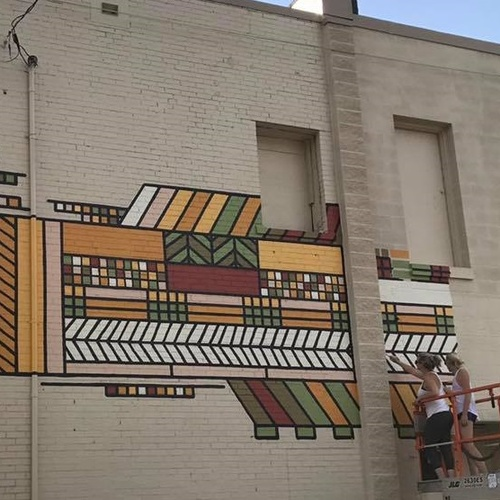 Mural being painted in downtown Mason City, Iowa by University of Iowa art student